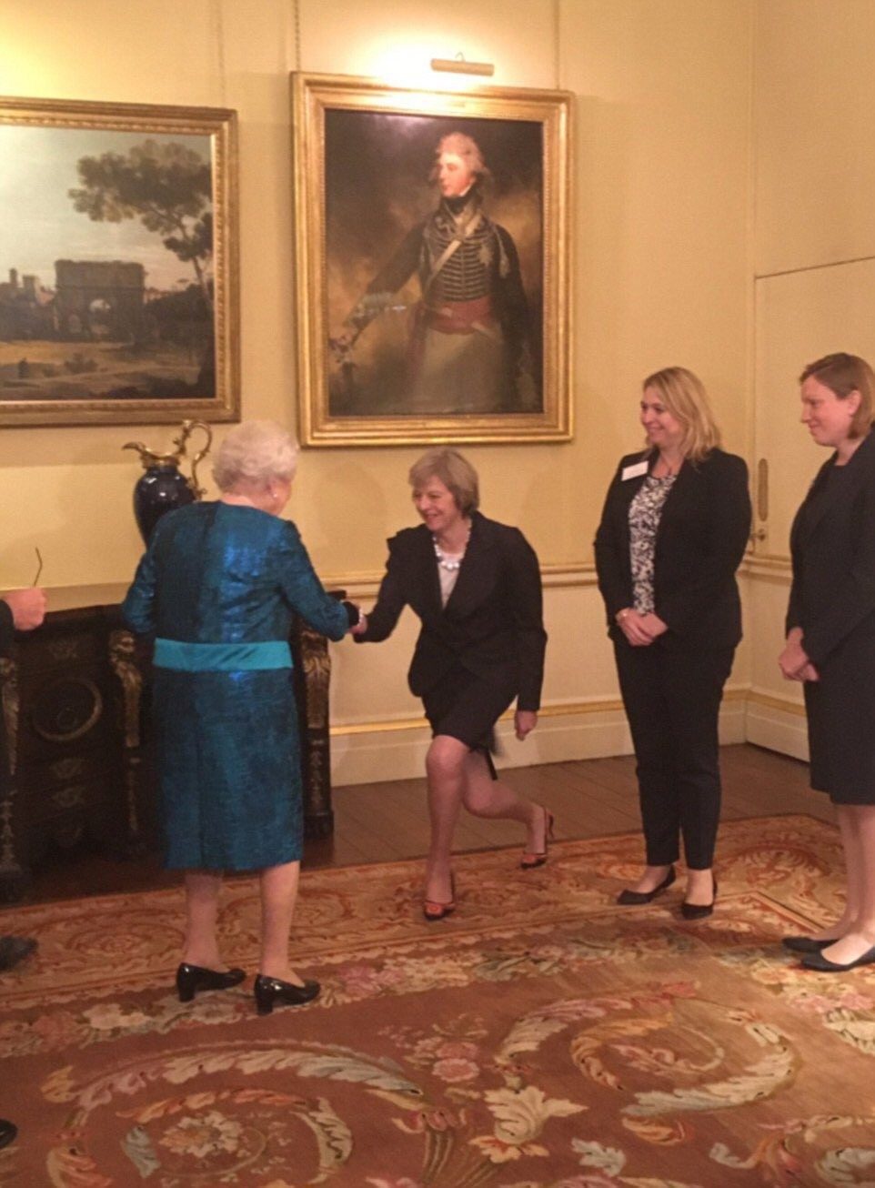 Theresa May Kneels To Greet Members Of The Royal Family